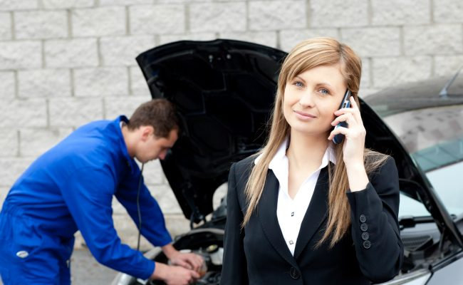 Man repairing car of business woman