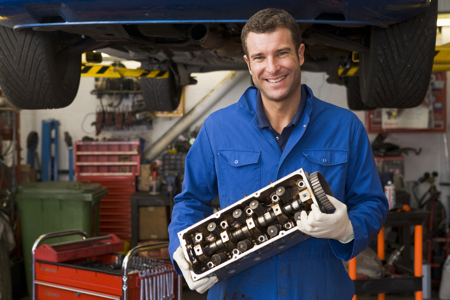 Mechanic holding car part smiling